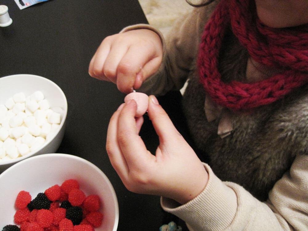 Auffädeln der Süßigkeiten auf die Kette