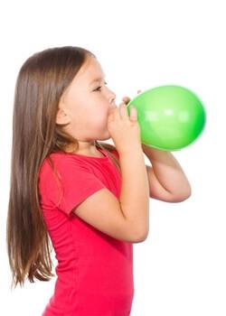 Mädchen spielt auf dem Kindergeburtstag mit Luftballon